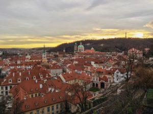 Pôr do sol sobre a cidade de Praga coberta de telhados vermelhos