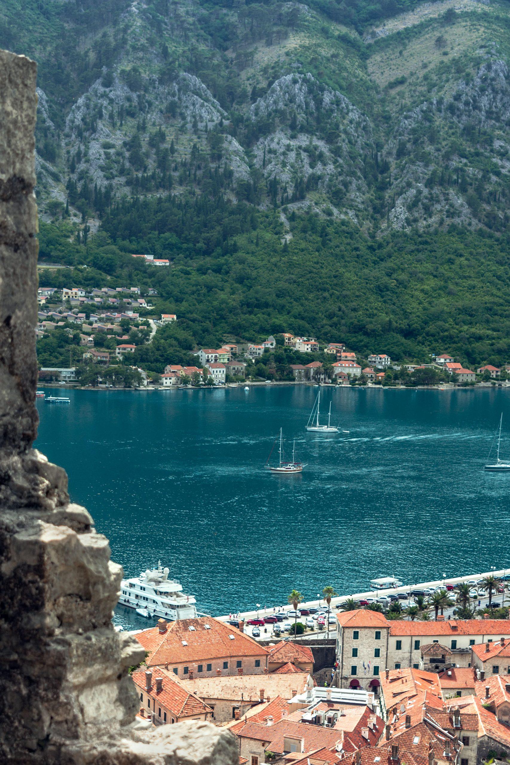 Vista para o mar Adriático das Muralhas de Kotor, que inclui os telhados alaranjados da cidade velha, e a água azul do mar