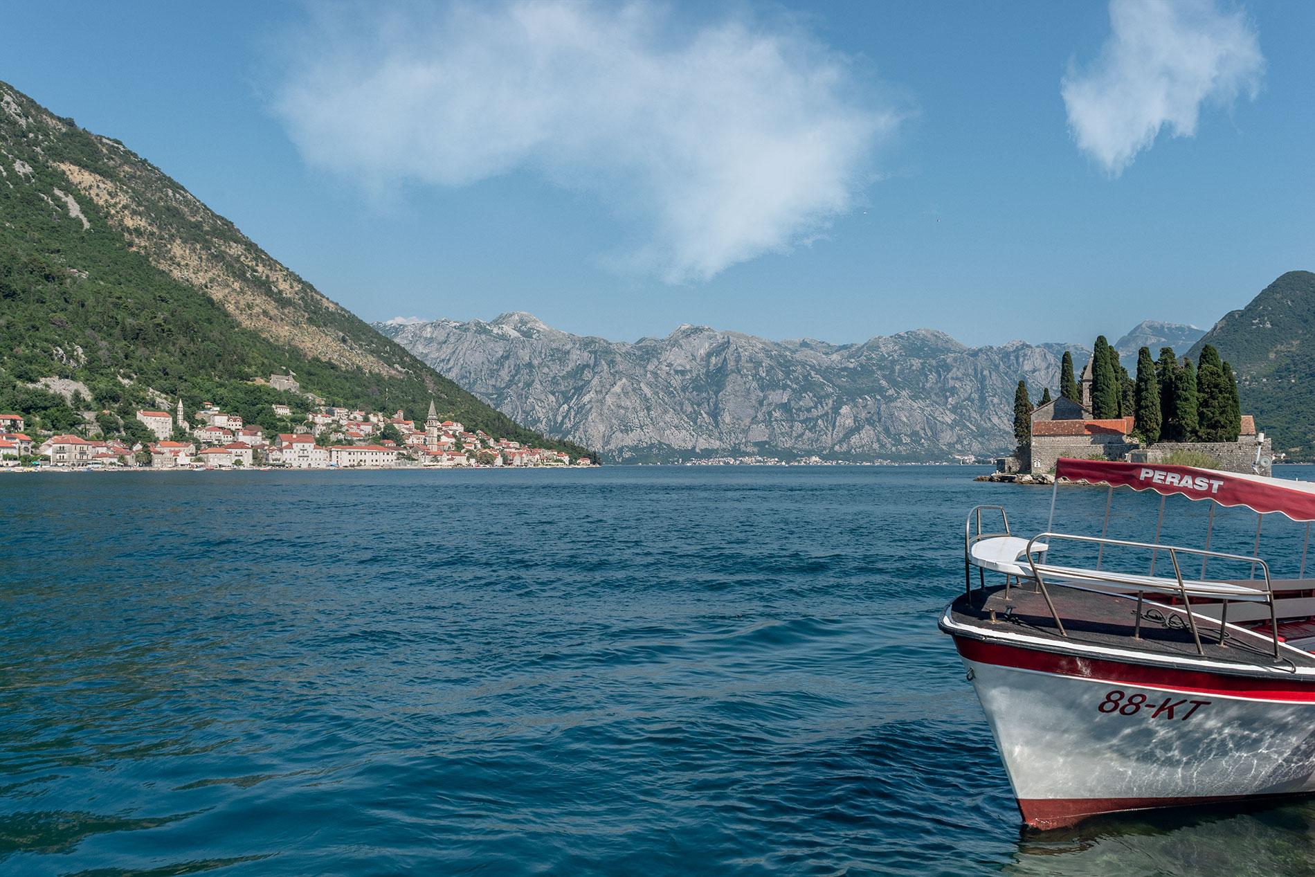 Um barco nas ilhas únicas localizadas na Baía de Kotor perto de Perast